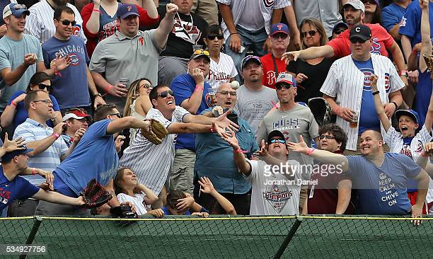 Fans scramble for a home run ball hit by Dexter Fowler of the Chicago Cubs against the Philadelphia Phillies in the 1st inning at Wrigley Field on...