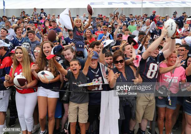 Fans scream for autographs from New England Patriots Coach Bill Belichick after the first day of training camp at the Gillette Stadium practice field...