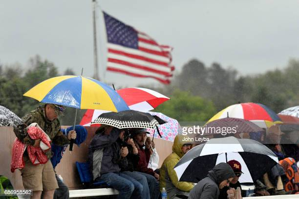 Fans seek shelter under umbrella as rain falls during the game with Mountain Vista and Rocky Mountain during the 2017 CHSAA Boys Baseball...