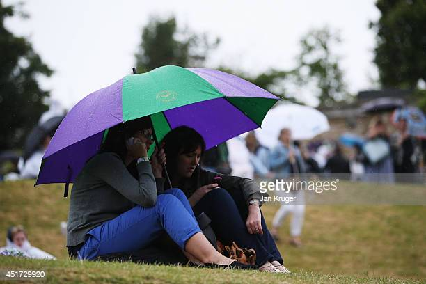 Fans shelter from the rain on Murray Mound on day twelve of the Wimbledon Lawn Tennis Championships at the All England Lawn Tennis and Croquet Club...