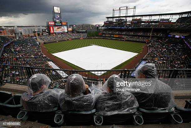 Fans shelter themselves from the rain and the tarp covers the infield as weather delays the start of the game between the San Francisco Giants and...