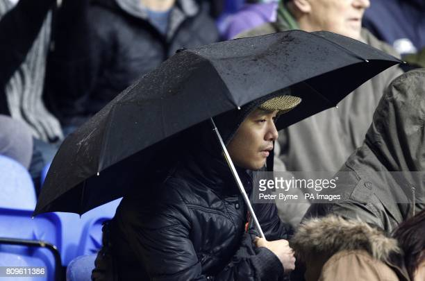 Fans shelter themselves from the rain with umbrella's in the stands