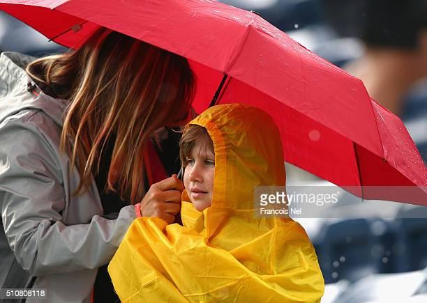 Fans shelter under umbrellas as rain delays play on day three of the WTA Dubai Duty Free Tennis Championship at the Dubai Duty Free Stadium on...