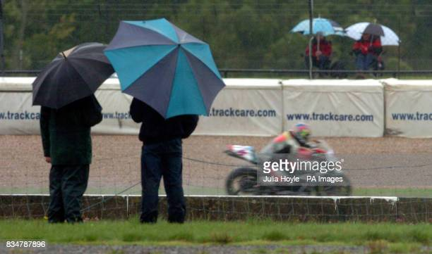 Fans shelter under umbrellas as they watch a practice session at Donington Park Castle Donington Derbyshire