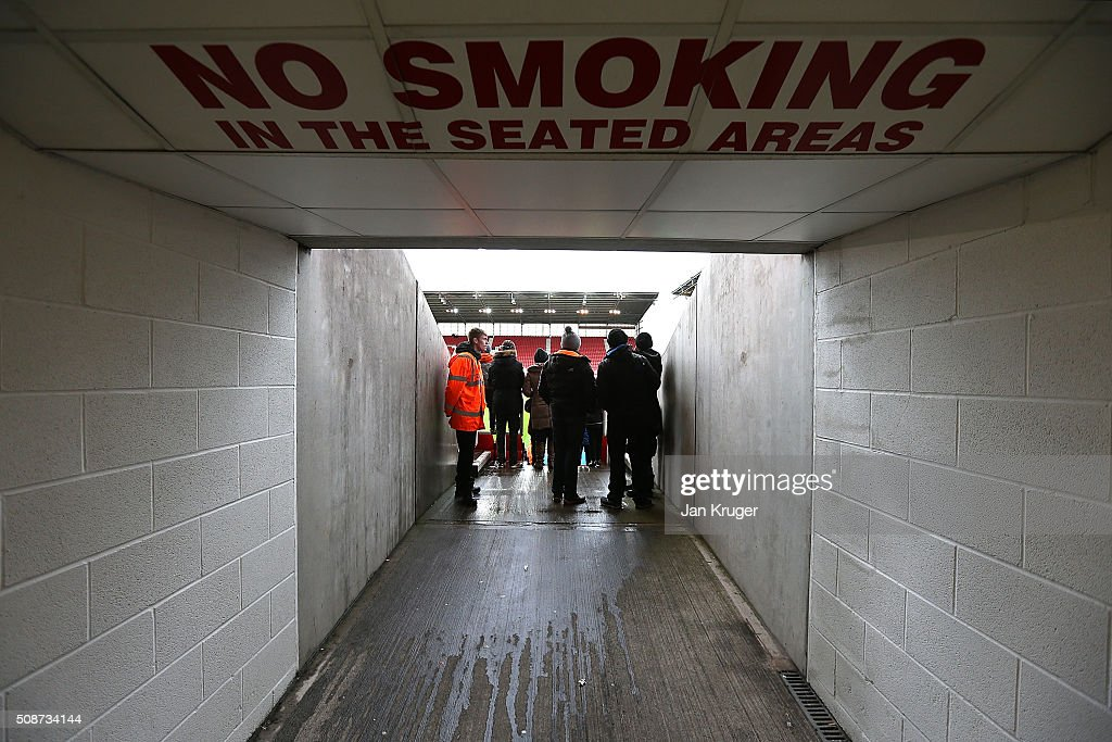 Fans shield from the rain in the corridor ahead of the Barclays Premier League match between Stoke City and Everton at Brittania Stadium on February 06, 2015 in Stoke on Trent, England.