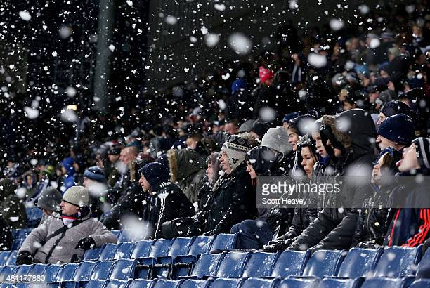 Fans shield from the snow during the Barclays Premier League match between West Bromwich Albion and Manchester City at The Hawthorns on December 26...