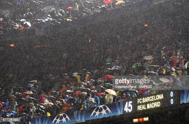 Fans shield themselves from the pouring rain with umbrella's in the stands