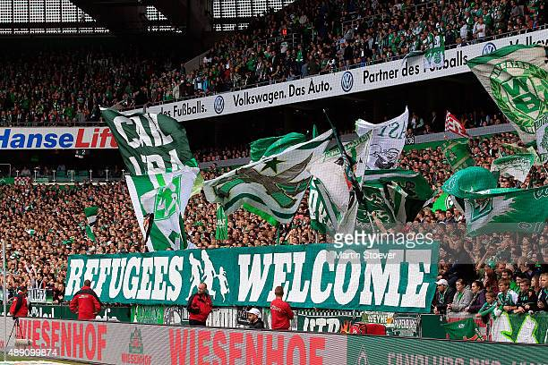 Fans show a banner reading 'refugees welcome' during the Bundesliga match between Werder Bremen and FC Ingolstadt at Weserstadion on September 19...