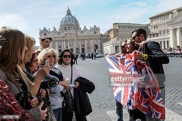 Fans show English flags as they wait in Saint Peter's Square the arrival of Queen Elizabeth II on April 3 2014 in Rome Italy During their brief visit...