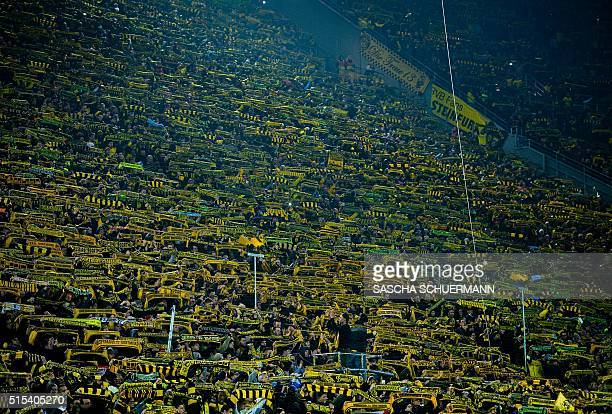 Fans show their scarves as a sign of respect following the death of a fan during the German first division Bundesliga football match Borussia...