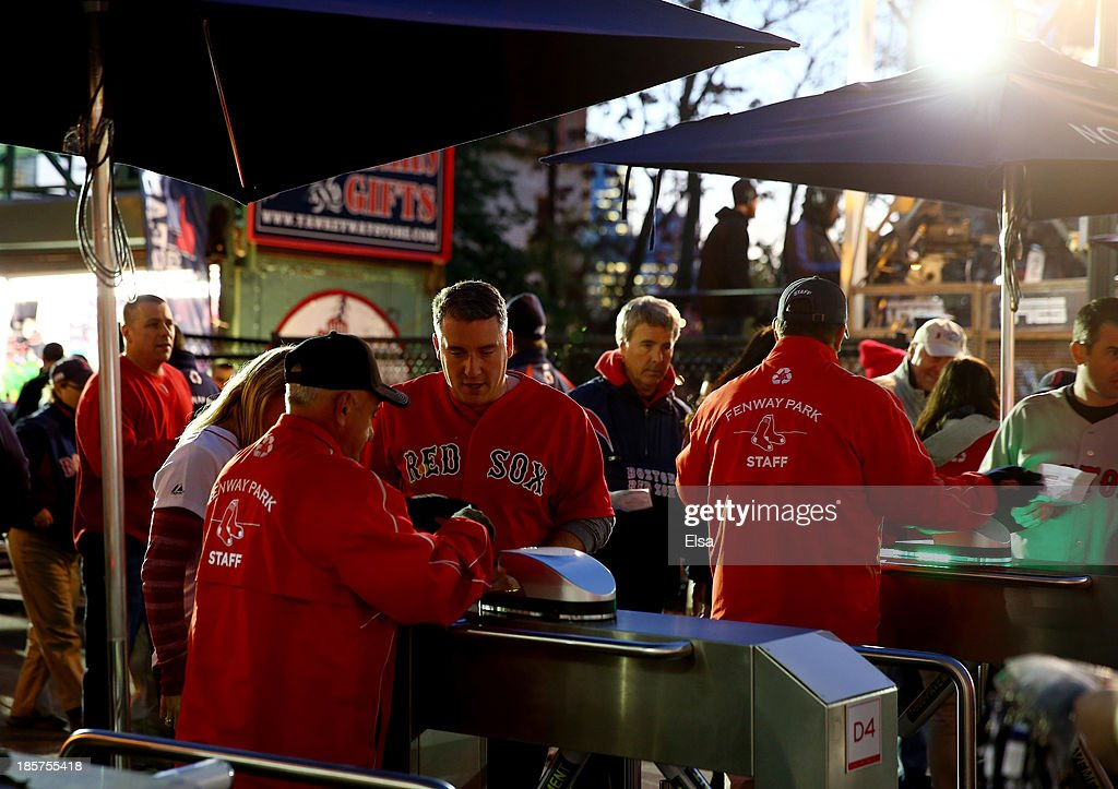 Fans show their tickets as they enter Fenway Park before Game Two of the 2013 World Series between the Boston Red Sox and the St. Louis Cardinals at Fenway Park on October 24, 2013 in Boston, Massachusetts.