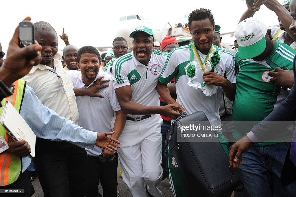 Fans sing to praise midfielder John Oli Mikel's luggage on arrival at the airport in Abuja on February 12, 2013. The newly crowned African champions Nigerian Super Eagles arrives in Abuja to a warm reception by fans and government officials after defeating Burkina Faso to win the 2013 African Cup of Nations in South Africa.
