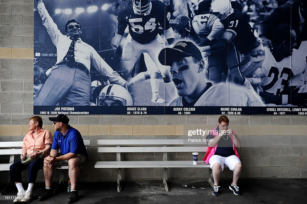 Fans sit in front of a former Penn State football coach Joe Paterno sign inside Beaver Stadium during play between the Penn State Nittany Lions and the Ohio Bobcats on September 1, 2012 in State College, Pennsylvania.