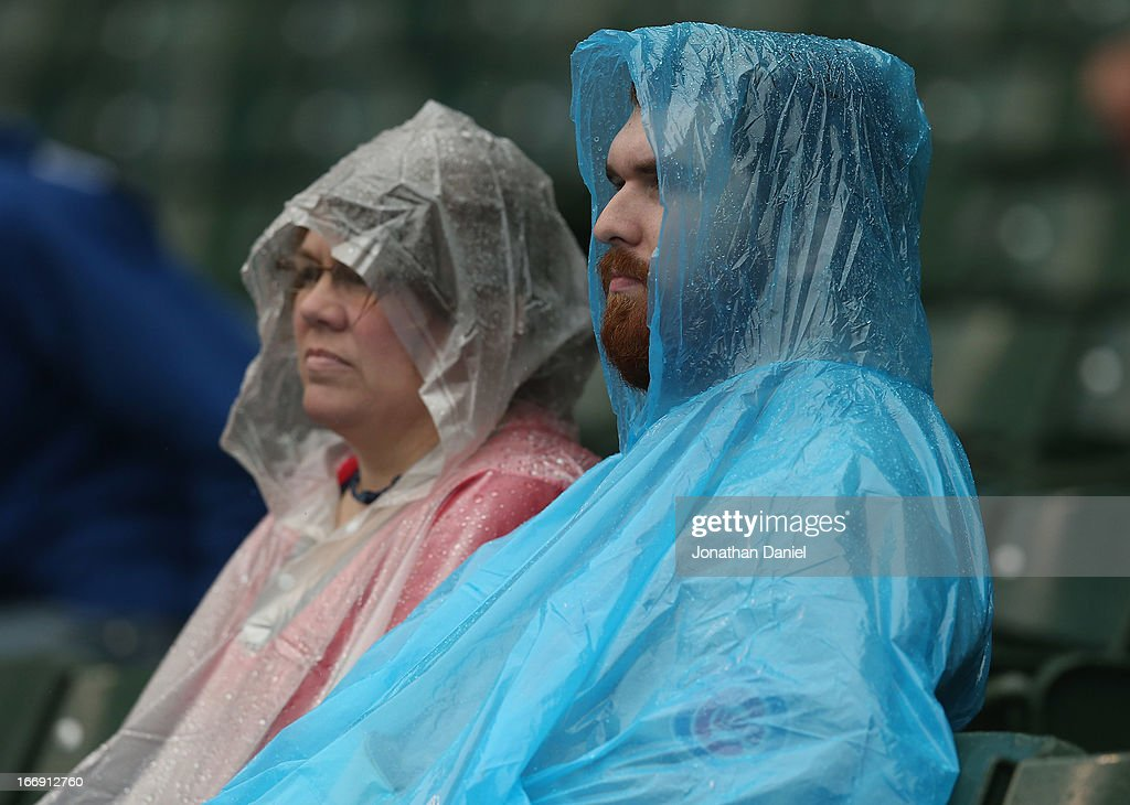 Fans sit in the rain as the Chicago Cubs take on the Texas Rangers at Wrigley Field on April 18, 2013 in Chicago, Illinois.