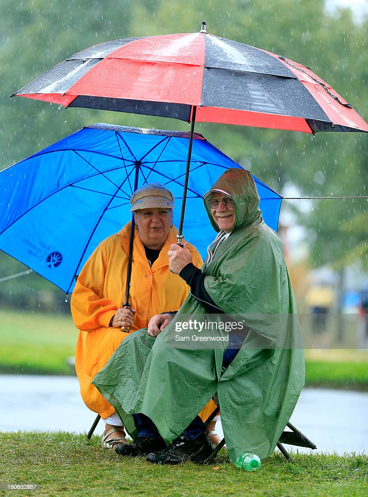 Fans sit in the rain with umbrellas as play is suspended due to inclement weather during the Final Round of the BMW Championship at Conway Farms Golf Club on September 15, 2013 in Lake Forest, Illinois.