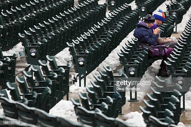 Fans sit in the snow covered seating bowl as snow removal delays the start of the double header between the New York Mets and the Colorado Rockies at...