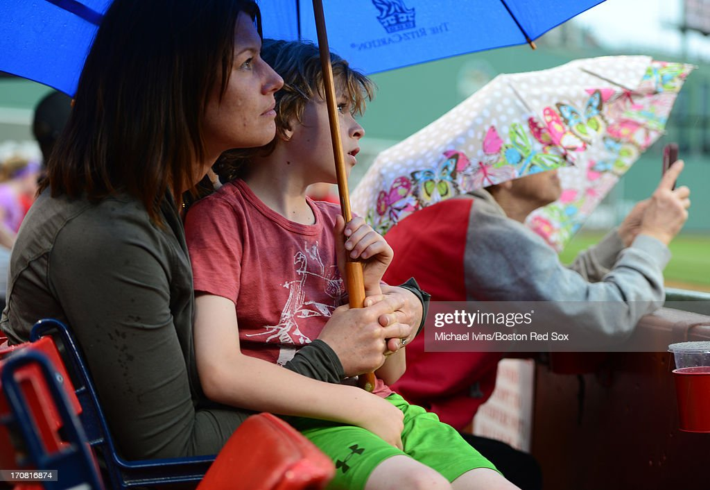 Fans sit under umbrellas during a rain delay in the fifth inning of a game between the Boston Red Sox and the Tampa Bay Rays on June 18, 2013 at Fenway Park in Boston, Massachusetts.