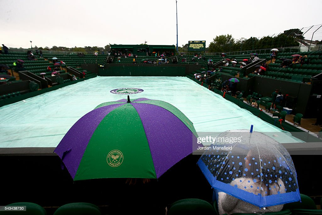 Fans sit under umbrellas on court three as rain delays play during day two of the Wimbledon Lawn Tennis Championships at the All England Lawn Tennis and Croquet Club on June 28, 2016 in London, England.