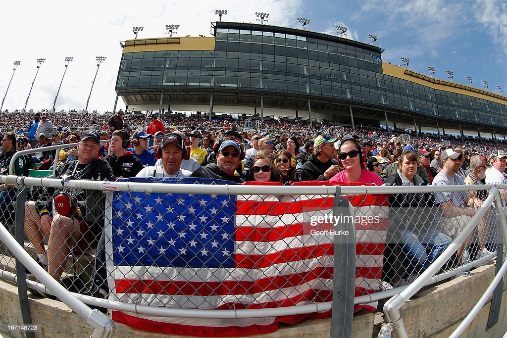 Fans sit with an american flag in the stands during the NASCAR Sprint Cup Series STP 400 at Kansas Speedway on April 21, 2013 in Kansas City, Kansas.