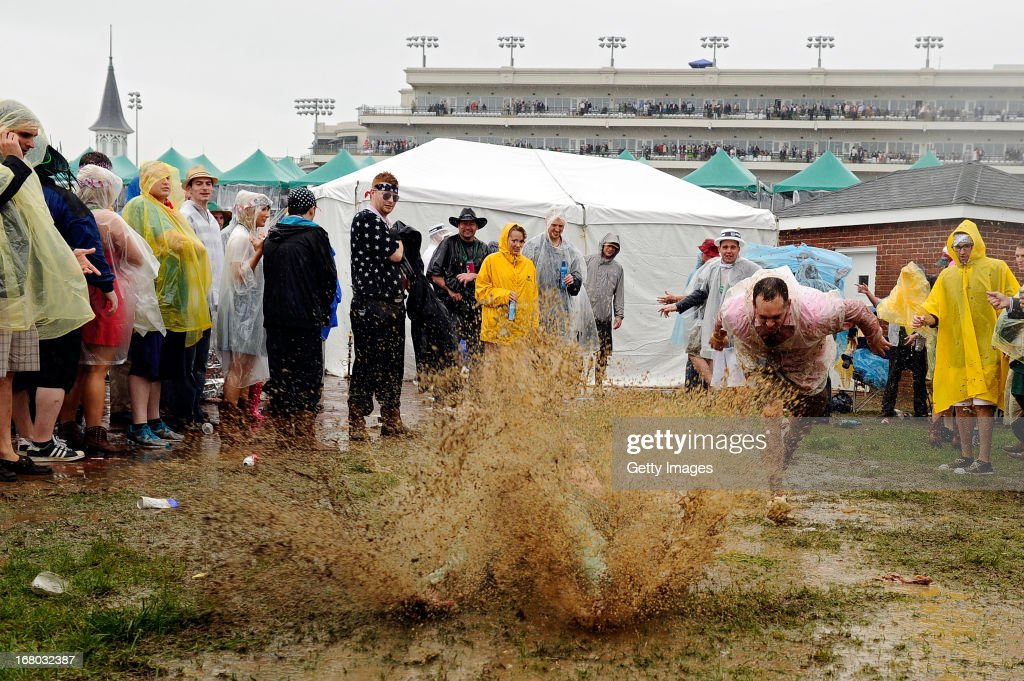 Fans slide through the mud in the infield prior to the 139th running of the Kentucky Derby at Churchill Downs on May 4, 2013 in Louisville, Kentucky.