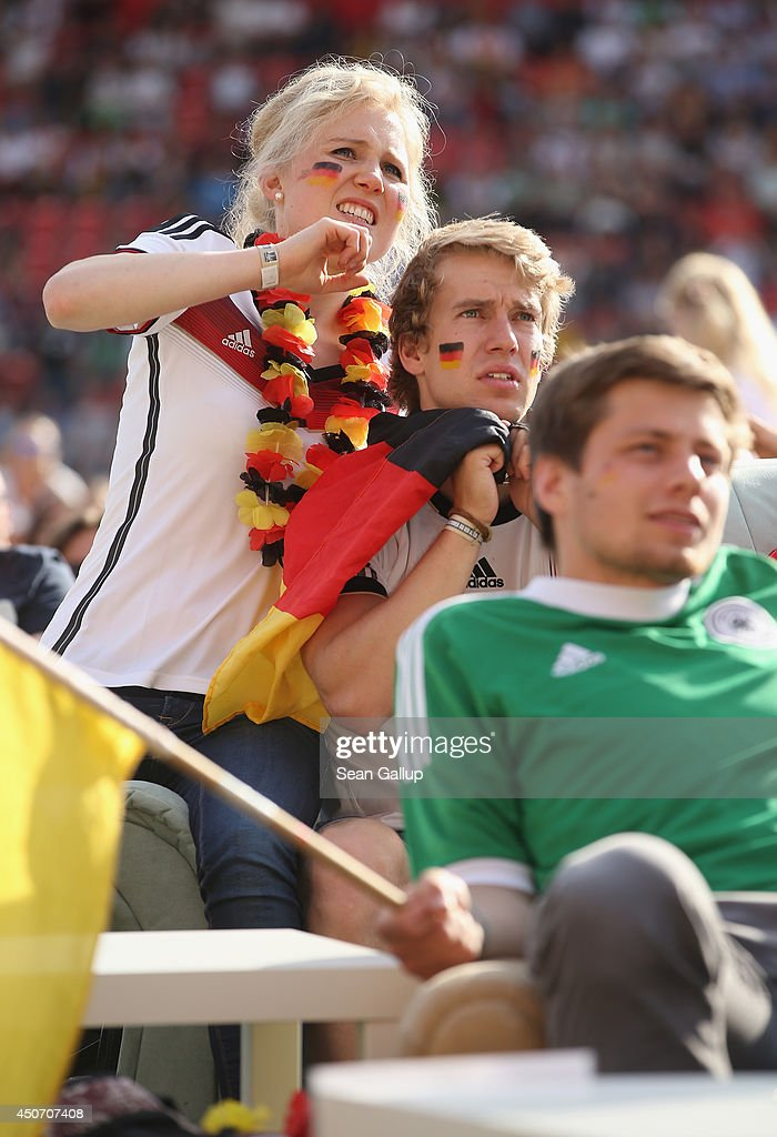 Fans, some of them draped in German flags, react to play as they watch the Germany-Portugal World Cup match at a public viewing at the Alte Foersterei FC Union stadium on June 16, 2014 in Berlin, Germany. The stadium has allowed fans to bring 700 sofas that they've set up on the lawn to watch the World Cup matches on a giant monitor.