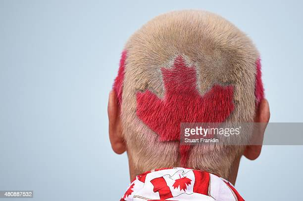 A fans sports a Canadian flag hairstyle as he follows Graham Delaet of Canada during the first round of the 144th Open Championship at The Old Course...