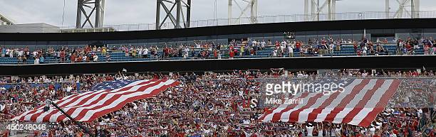 Fans stand and hold two flags for the United States national anthem before the international friendly match against Nigeria at EverBank Field on June...