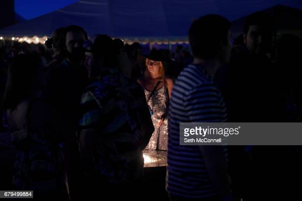 Fans stand around a propane fire pit during the Big Wonderful at the former Denver Post Printing Plant on May 5 in Denver Colorado