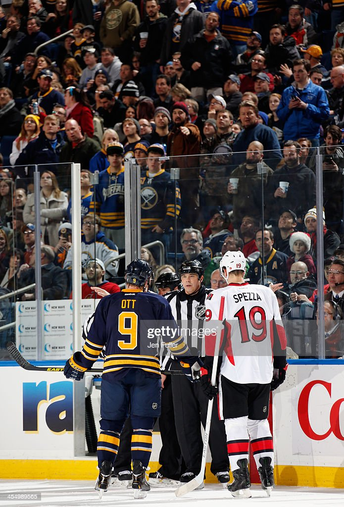 Fans stand as Steve Ott #9 of the Buffalo Sabres and Jason Spezza #19 of the Ottawa Senators wait while a play is reviewed at First Niagara Center on December 10, 2013 in Buffalo, New York.
