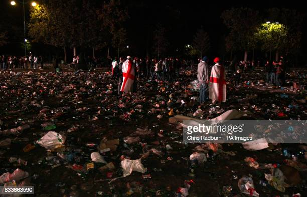 Fans stand dejected amongst the rubbish after watching the English Rugby team lose the Rugby World Cup Final Match on an outdoor big screen near the...