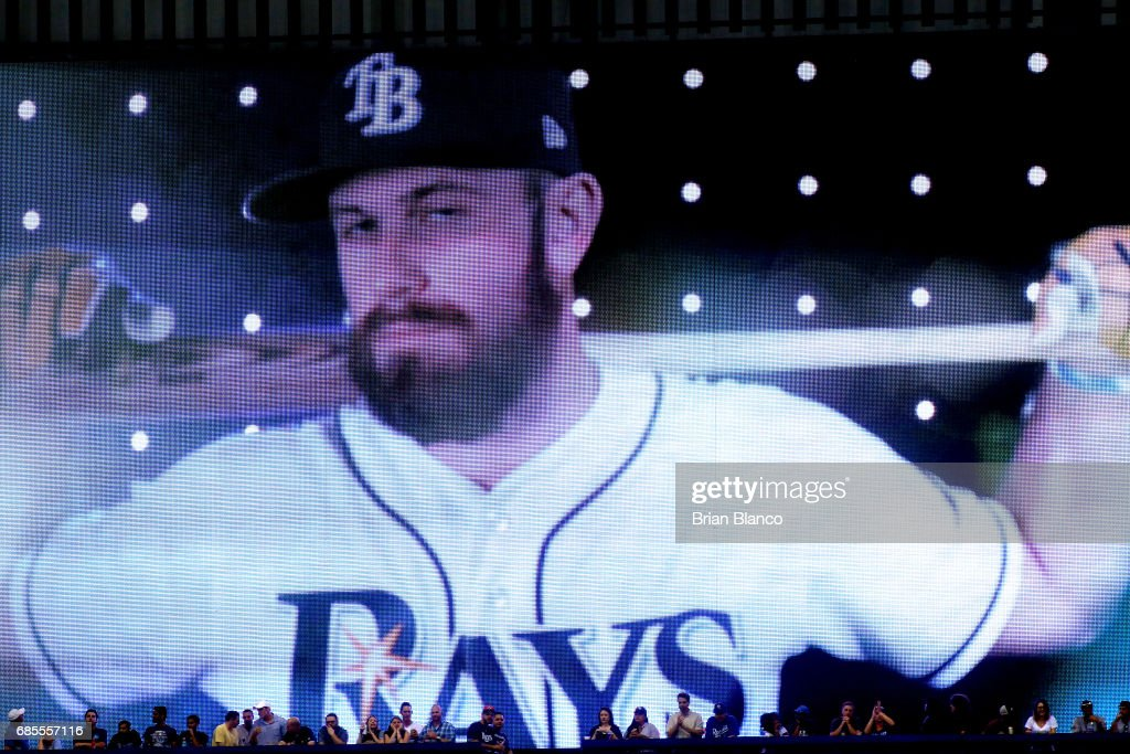 Fans stand in front of a large screen as they watch Evan Longoria of the Tampa Bay Rays come up to bat during the seventh inning of a game against the New York Yankees on May 19, 2017 at Tropicana Field in St. Petersburg, Florida.