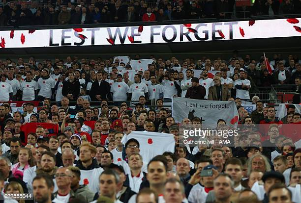 Fans stand in front of sign saying Lest we forget as they observe a moment for remembrance day during the FIFA 2018 World Cup Qualifier between...