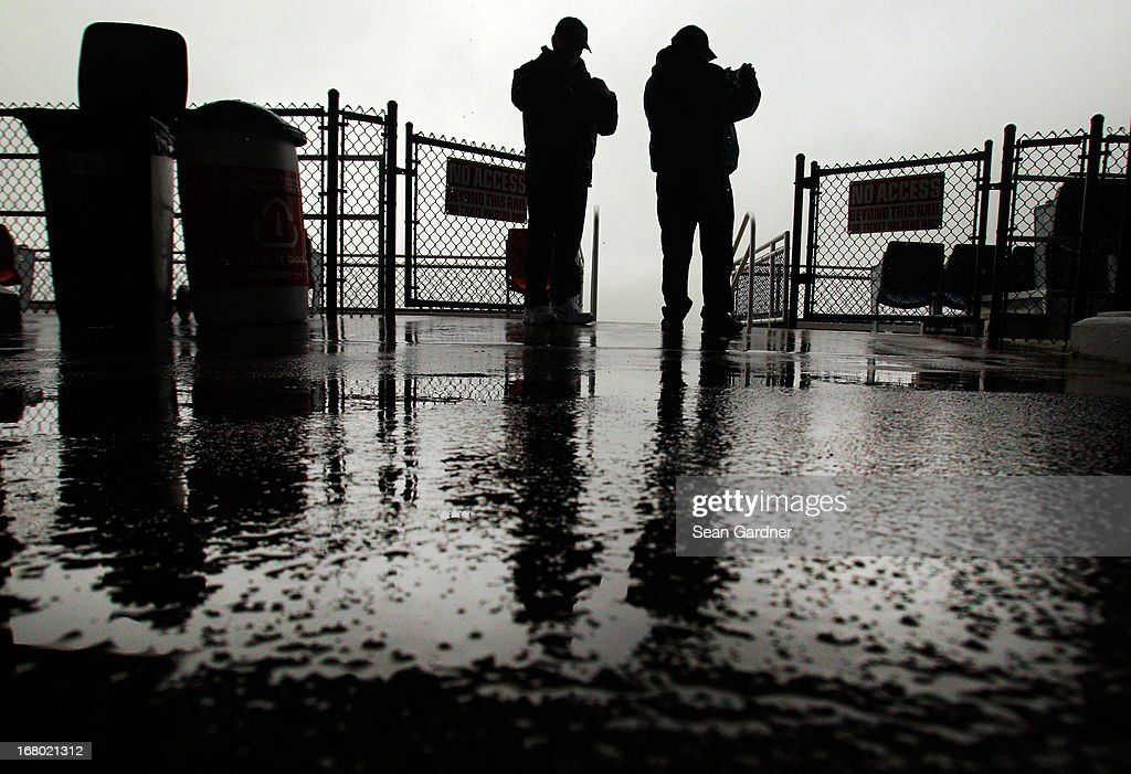 Fans stand on a platform at the top of the grandstand to avoid standing in the rain during qualifying for the NASCAR Sprint Cup Series Aaron's 499 at Talladega Superspeedway on May 4, 2013 in Talladega, Alabama.