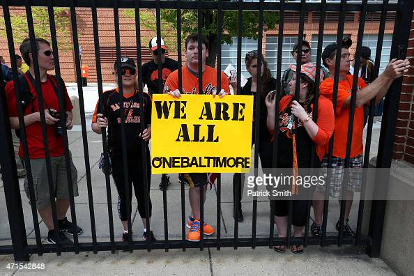 Fans stand outside of the ballpark as the Baltimore Orioles play the Chicago White Sox at an empty Oriole Park at Camden Yards on April 29 2015 in...