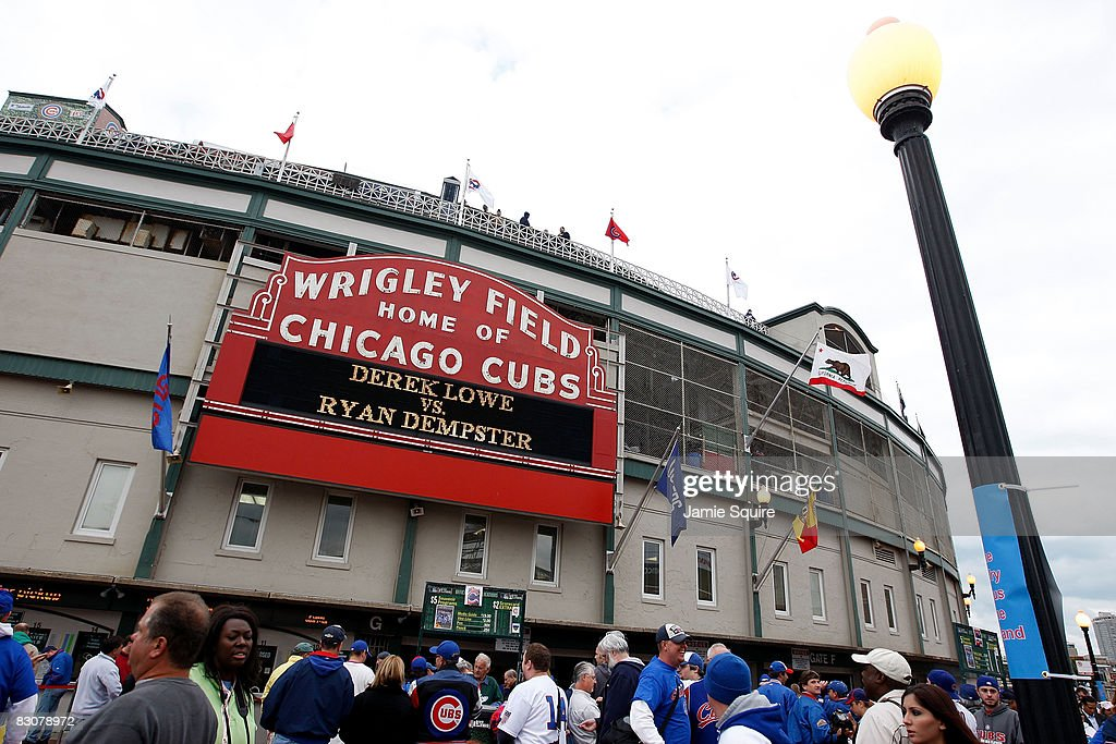 Fans stand outside Wrigley Field under the famous marquee, which displays tonights pitching match up 'Derek Lowe vs. Ryan Dempster', prior to the Chicago Cubs hosting the Los Angeles Dodgers in Game One of the NLDS during the 2008 MLB Playoffs at Wrigley Field on October 1, 2008 in Chicago, Illinois.