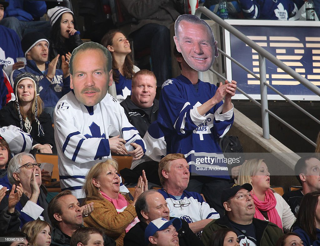 Fans standing and wearing alumni masks featuring Wendel Clark and Johnny Bower during a game between the Winnipeg Jets and the Toronto Maple Leafs on March 16, 2013 at the Air Canada Centre in Toronto, Ontario, Canada. The Jets defeated the Leafs 5-4 in an overtime shootout.
