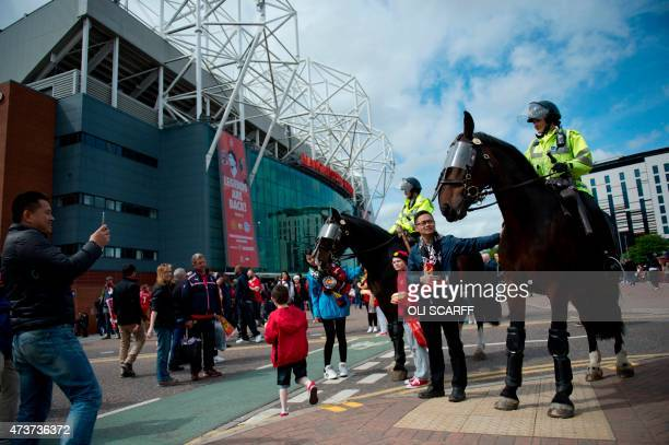 Fans stroke police horses outside Old Trafford stadium before the English Premier League football match between Manchester United and Arsenal at Old...