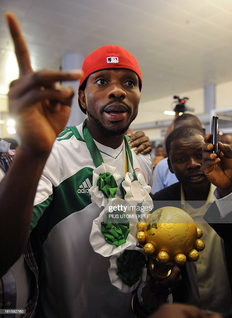 Fans struggle to touch the Africa Cup of Nations trophy hold by skipper of the Nigerian football team Joseph Yobo upon arrival in Abuja on February 12, 2013. The newly crowned African champions Nigerian Super Eagles arrives in Abuja to a warm reception by fans and government officials after defeating Burkina Faso to win the 2013 African Cup of Nations in South Africa. AFP PHOTO/ PIUS UTOMI EKPEI