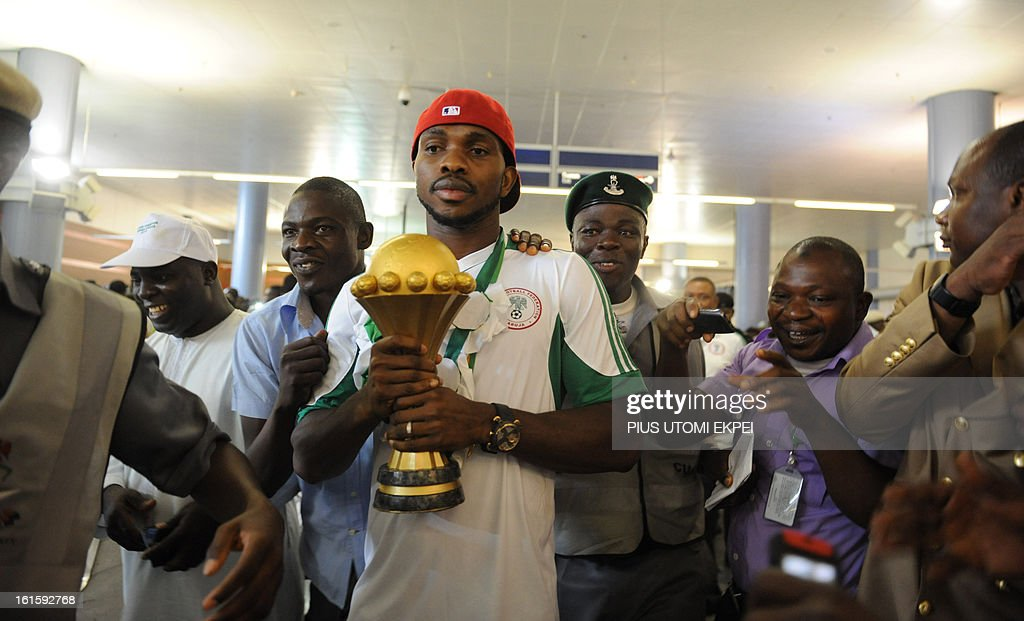 Fans struggle to touch the Africa Cup of Nations trophy hold by skipper of the Nigerian football team Joseph Yobo upon arrival in Abuja on February 12, 2013. The newly crowned African champions Nigerian Super Eagles arrives in Abuja to a warm reception by fans and government officials after defeating Burkina Faso to win the 2013 African Cup of Nations in South Africa.