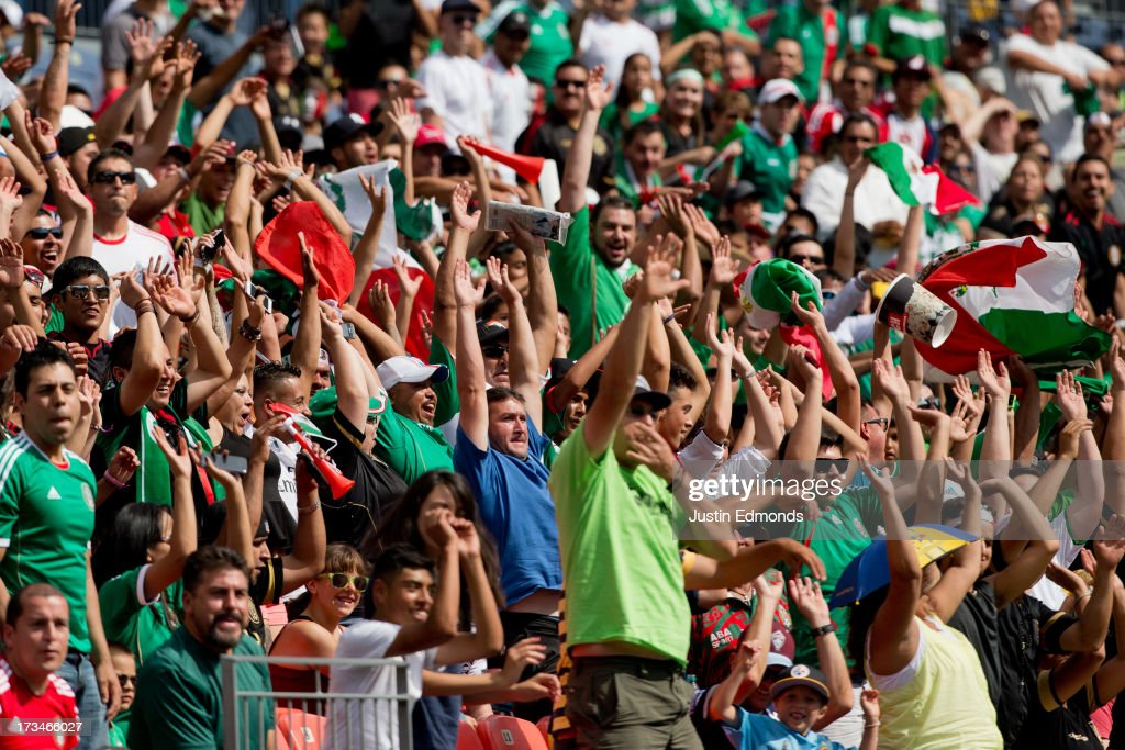 Fans support Mexico by doing the wave during the first half of a CONCACAF Gold Cup match against Martinique at Sports Authority Field at Mile High on July 14, 2013 in Denver, Colorado.
