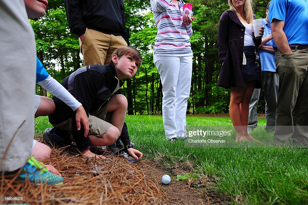 Fans surround a golf ball that Phil Mickelson hit out of bounds into a yard near the 15th fairway during the third round of the Wells Fargo Championship at Quail Hollow Club in Charlotte, North Carolina, Saturday, May 4, 2013.