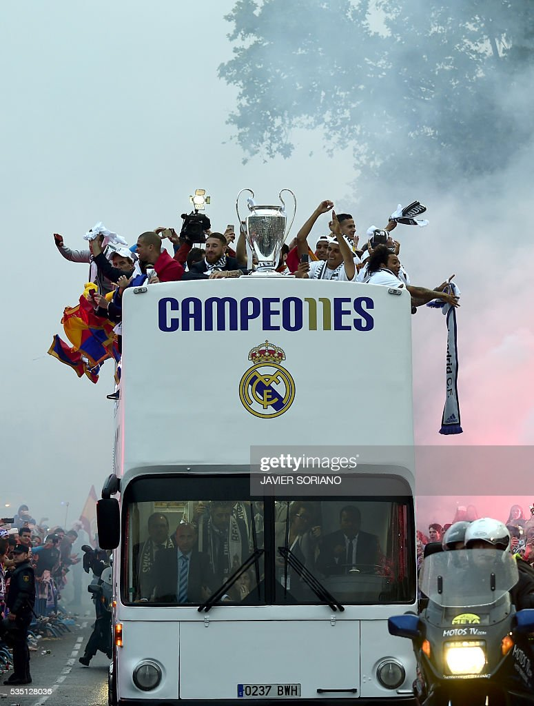 Fans surround the bus as Real Madrid players hold up the trophy celebrating the team's win on Plaza Cibeles in Madrid on May 29, 2016 after the UEFA Champions League final foobtall match between Real Madrid CF, Club Atletico de Madrid held in Milan, Italy. / AFP / JAVIER
