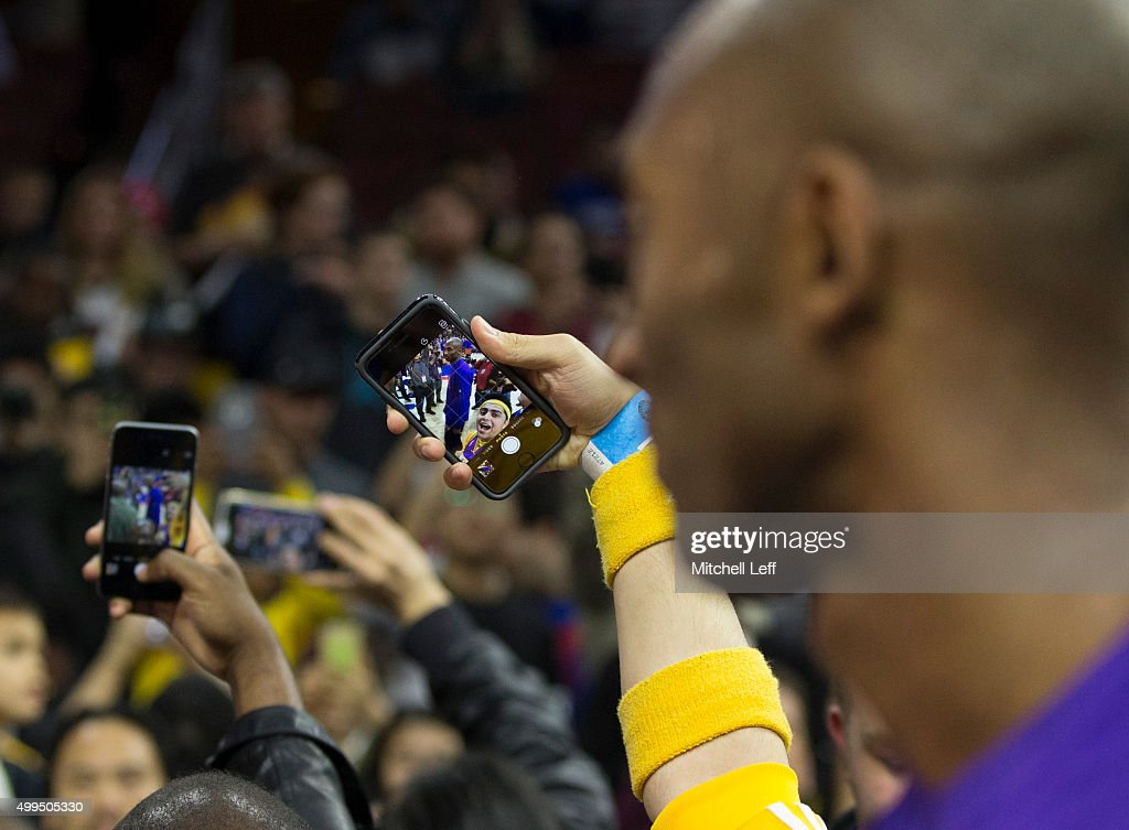 Fans take a selfie of Kobe Bryant of the Los Angeles Lakers prior to the game against the Philadelphia 76ers on December 1 2015 at the Wells Fargo...