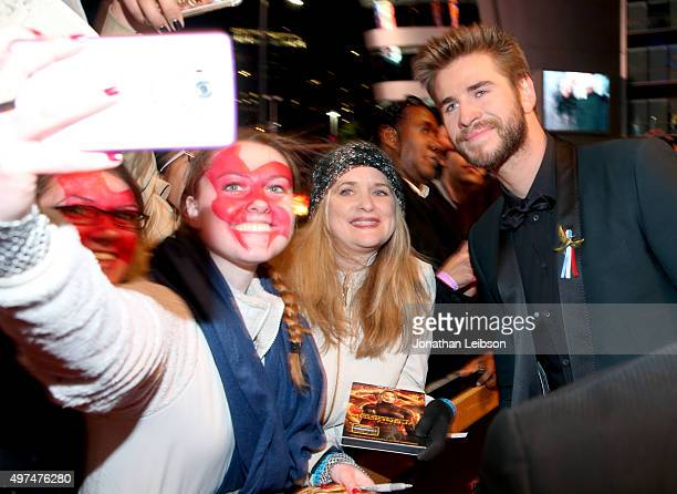 Fans take a Selfie with actor Liam Hemsworth at the premiere of The Hunger Games Mockingjay – Part 2 on November 16 2015 in Los Angeles California