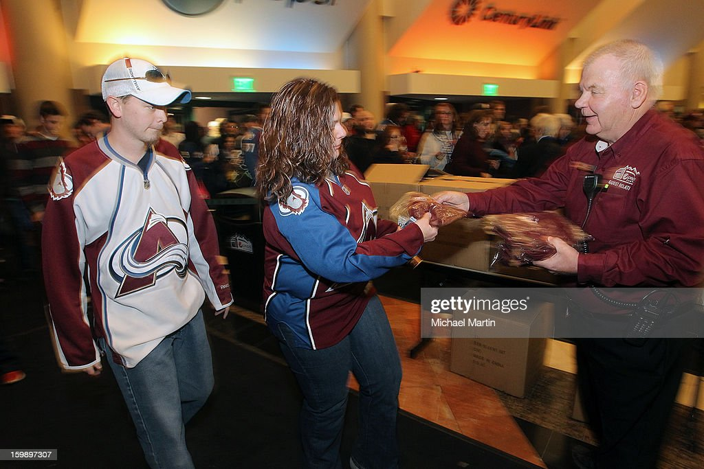 Fans take complimentary hats from a Pepsi Center usher before the start of the Colorado Avalanche home opener against the Los Angeles Kings on January 22, 2013 in Denver, Colorado.