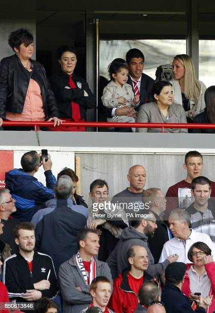 Fans take photographs of Liverpool's Luis Suarez sat in the stands