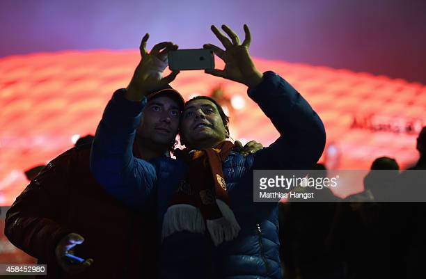 Fans take photographs prior to the UEFA Champions League Group E match between FC Bayern Munchen and AS Roma at Allianz Arena on November 5 2014 in...