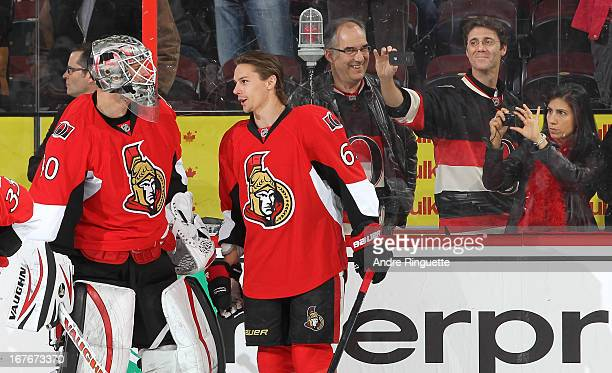 Fans take photos of Robin Lehner and Erik Karlsson of the Ottawa Senators as they talk during warmup prior to a game against the Philadelphia Flyers...