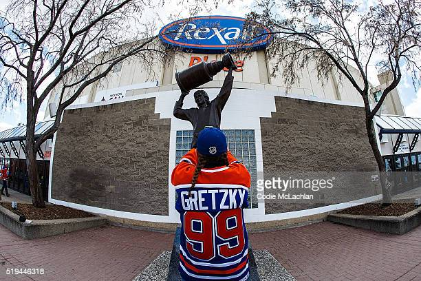 Fans take photos of the Wayne Gretzky statue outside of Rexall Place prior to the game between the Edmonton Oilers and the Vancouver Canucks on April...