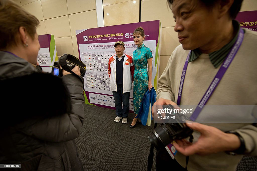 Fans take photos with Victoria Motrichko (2R) of the Ukraine following her second-place win at a draughts competition at the Beijing 2012 World Mind Games Tournament in Beijing on December 19, 2012. Some of the world's top chess players went eye-to-eye in the year's highest-level 'blindfold' chess tournament -- seen by some as the toughest challenge in the game. Unable to physically see their own or their opponent's past moves, the players summoned headache-inducing levels of concentration to fight for gold in a silent conference room, lined up in front of laptop screens showing a blank board. AFP PHOTO / Ed Jones